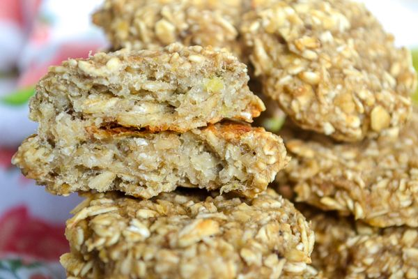 a stack of baby cookies cut open to see the dense oat and banana insides with a faded tea towel in the background