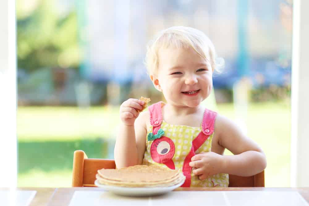 a baby girl in a pink and yellow shirt eating a stack of breast milk pancakes