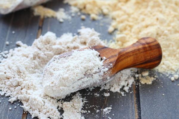 oat flour in a dark wooden scoop