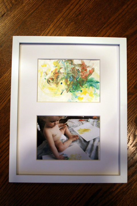 a 2 photo frame, one showing a child painting and the resulting finger painting in the other mat as a DIY gift for grandpa