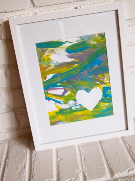 a photo of a framed finger painting with a white heart on the painting