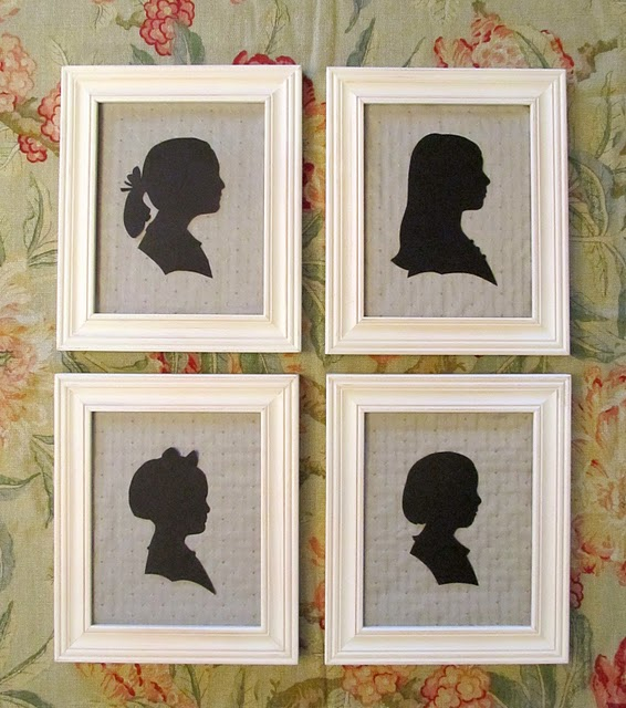 4 framed black silhouettes on a floral wallpapered wall