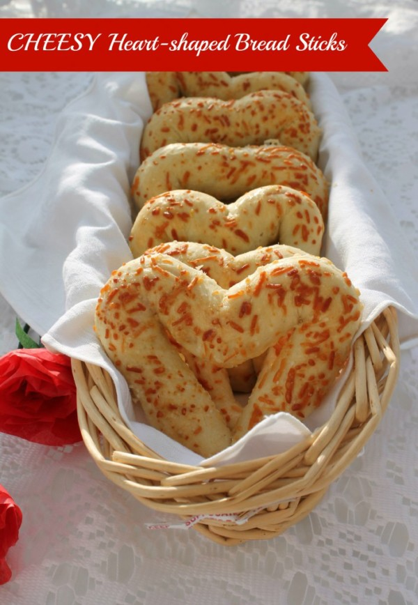 heart shaped food cheesy breadsticks in a wicker basket on top of a lace placemat