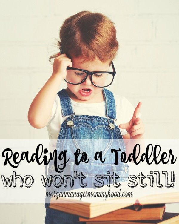 a cute toddler in a white tee shirt and overalls with big black rimmed glassed reading a book