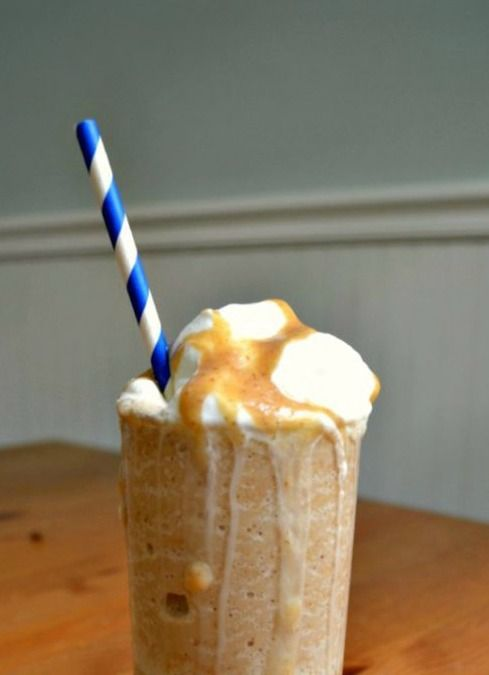 a homemade sugar free frappuccino with whipped cream drippin g down the sides of the cup with a blue and white straw