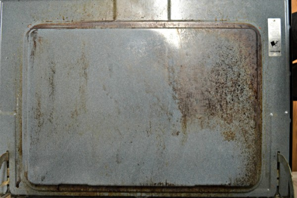 an oven door being cleaned without chemicals