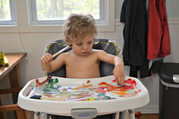A toddler in a highchair painting on the tray