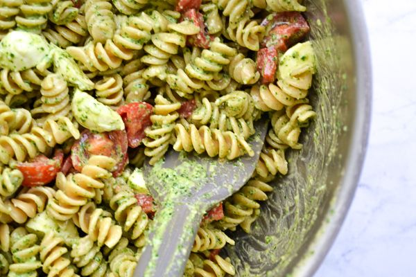 creamy pesto pasta salad in a large silver mixing bowl on a marble counter top with a gray rubber spatula