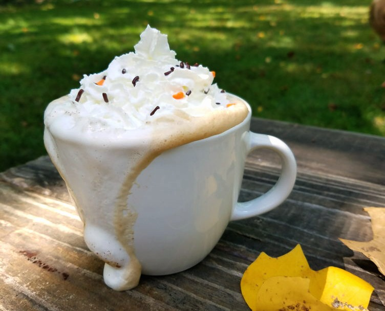 a white mug overflowing with sugar free pumpkin spice tipped with whipped cream on a wooden table in fall