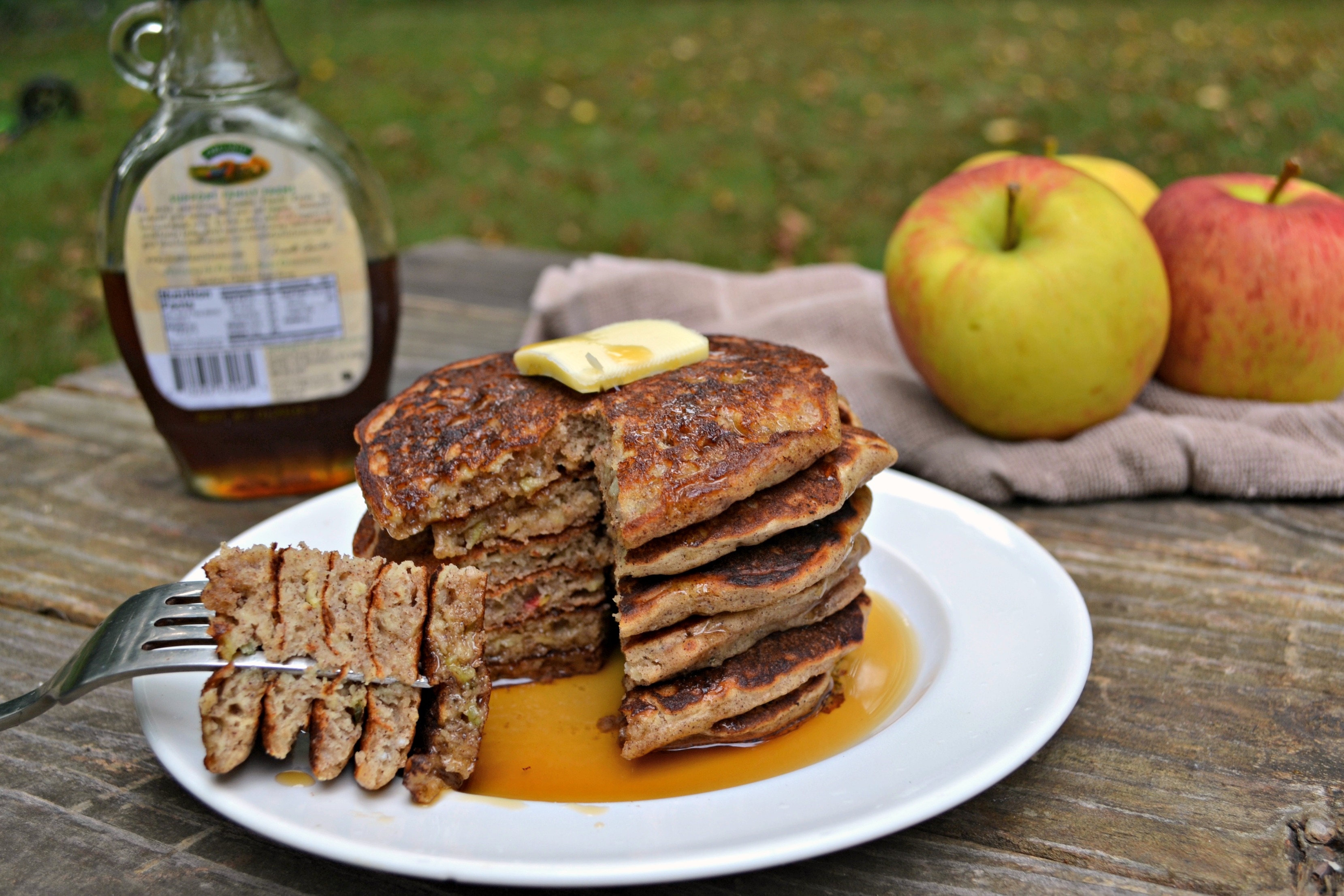 Stack of healthy apple pancakes on a white plate with a triangle bite being help on a a silver fork on a wooden picnic table. A pat of butter is melting on top and syrup is dripping down the sides with an glass bottle of syrup and apples on a brown dish towel in the background
