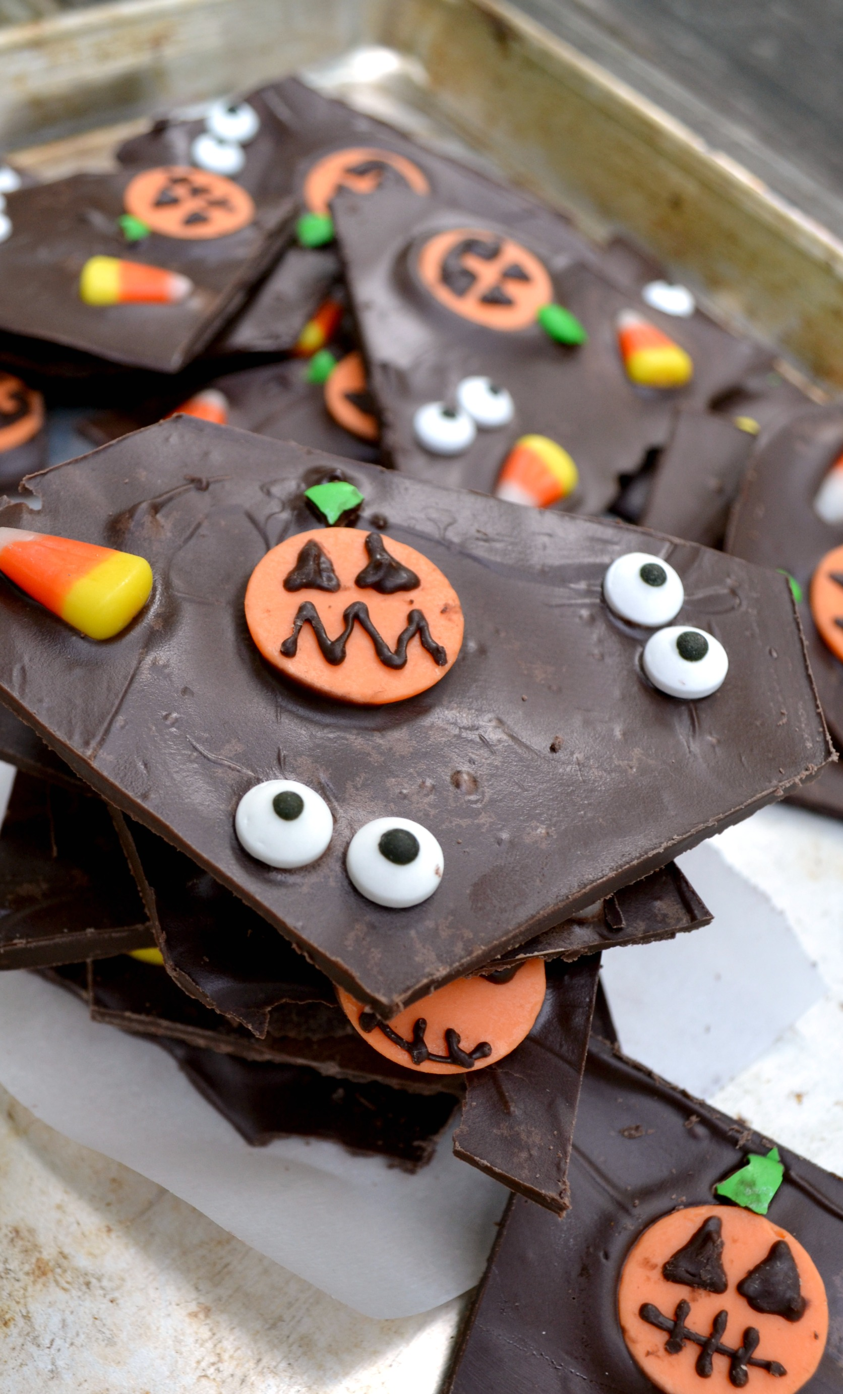 a pile of halloween bark with candy eyes pumpkins and candy corn