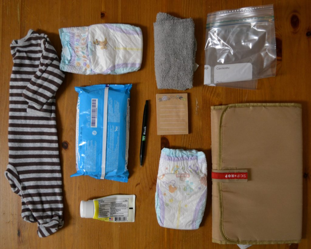 flat-lay image showing all of the components to pack into your car diaper changing station.