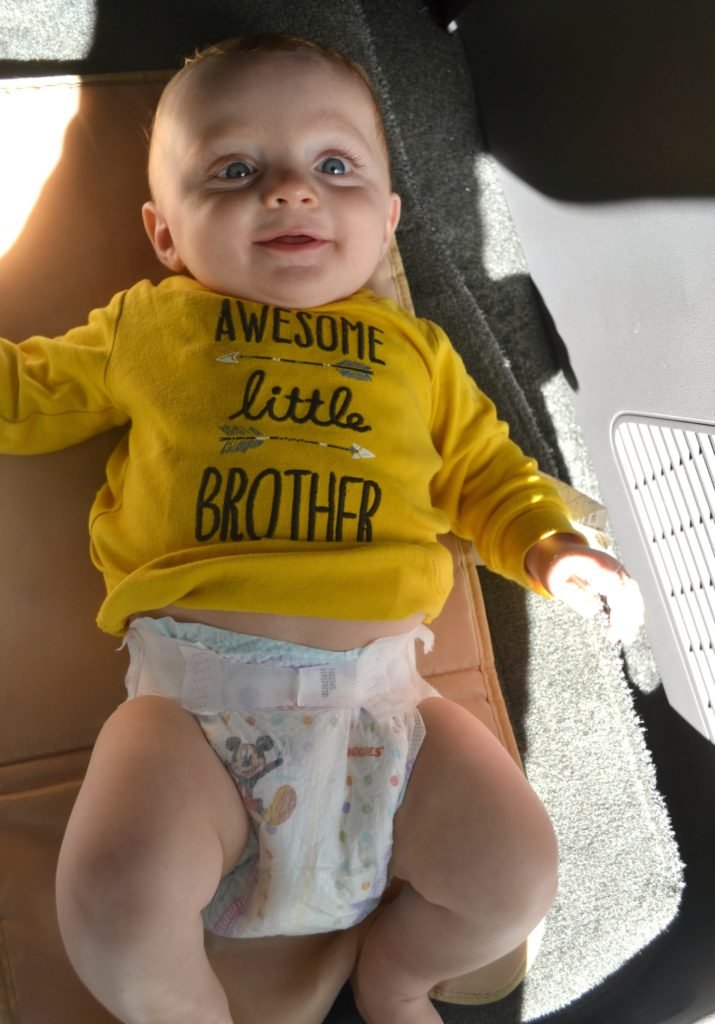 a baby getting a diaper change in the car with a yellow onesie and a diaper on