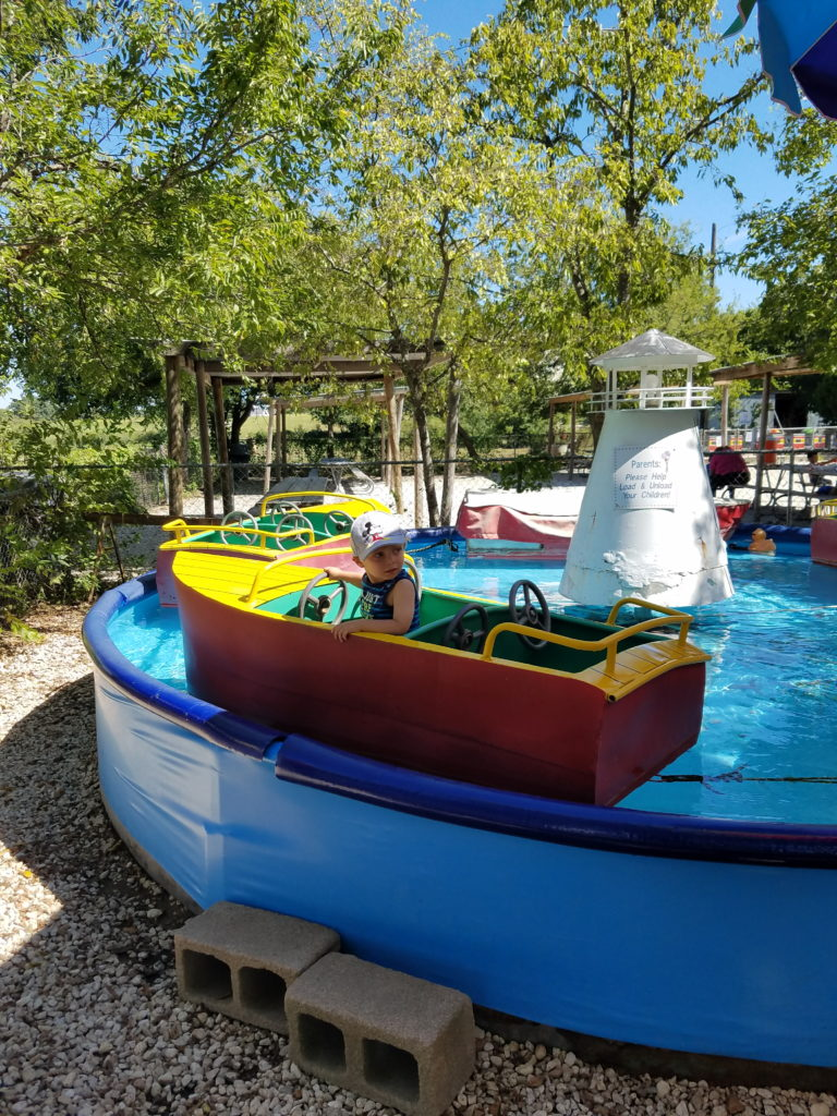 A boy sitting on a boat ride at Kiddie Acres in Austin, Texas