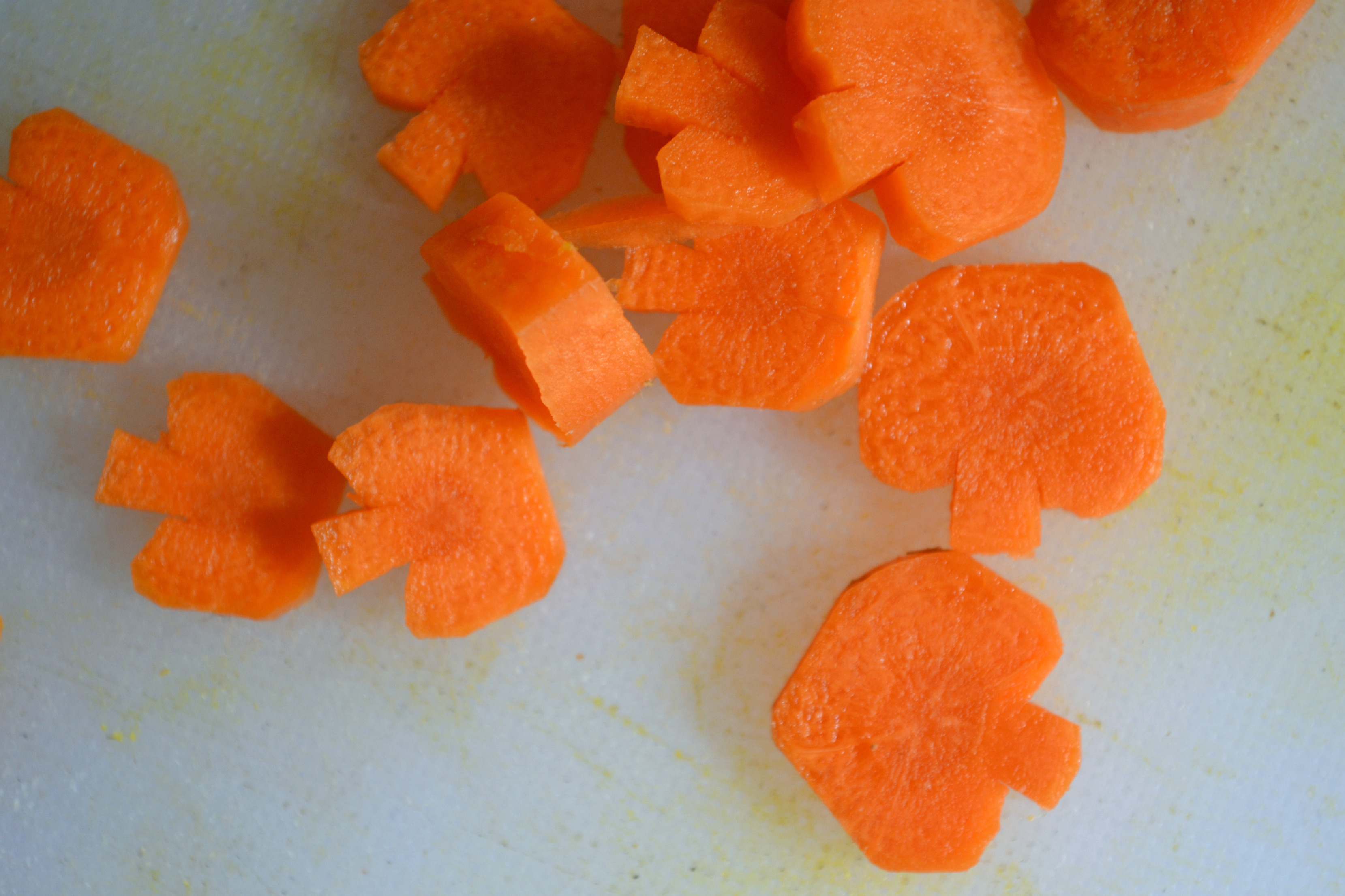 carrots cut into tiny pumpkins on a cutting board to add to soup