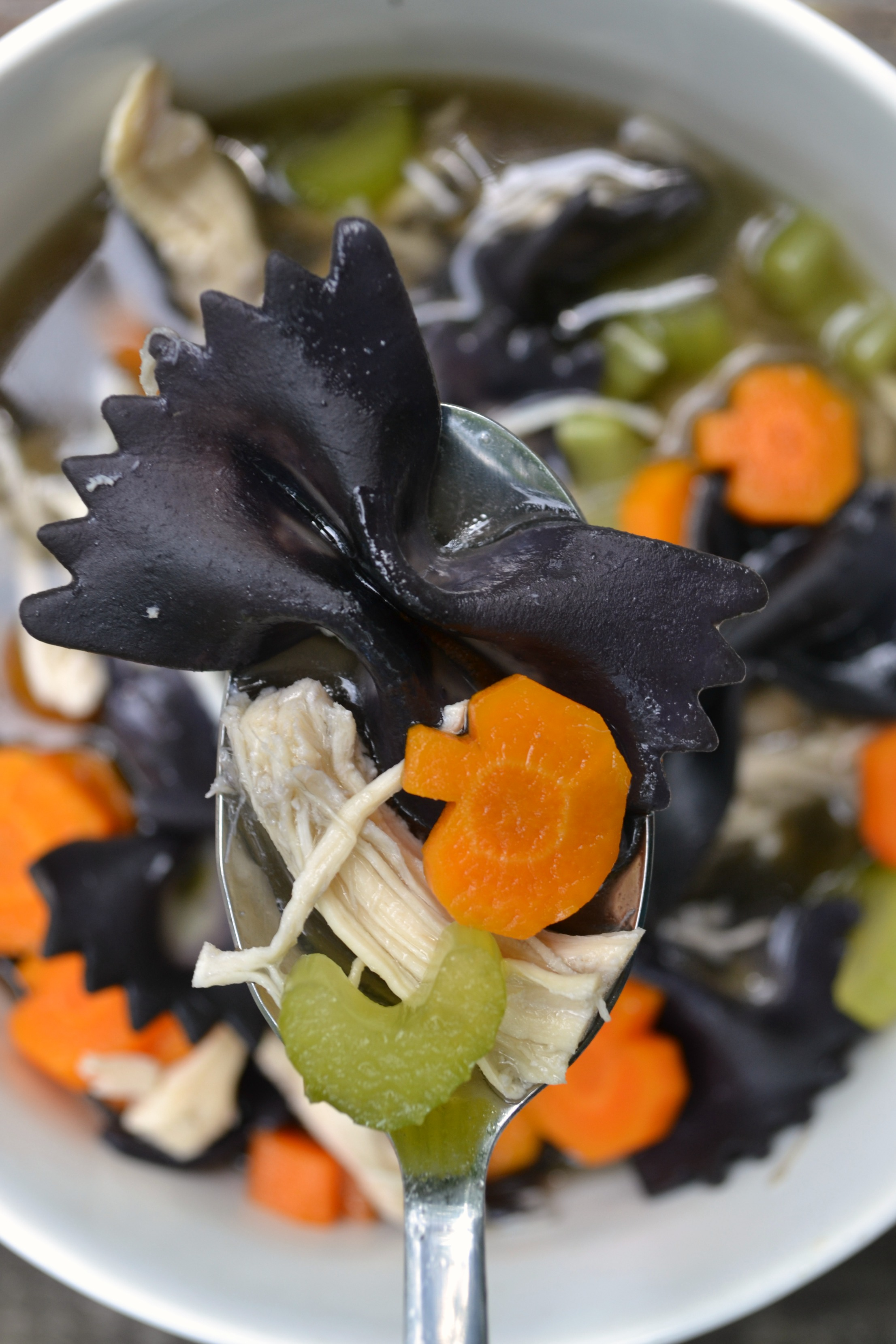 a photo showing a black bowtie noodle in a spoon with a pumpkin carrot for chicken boodle halloween soup