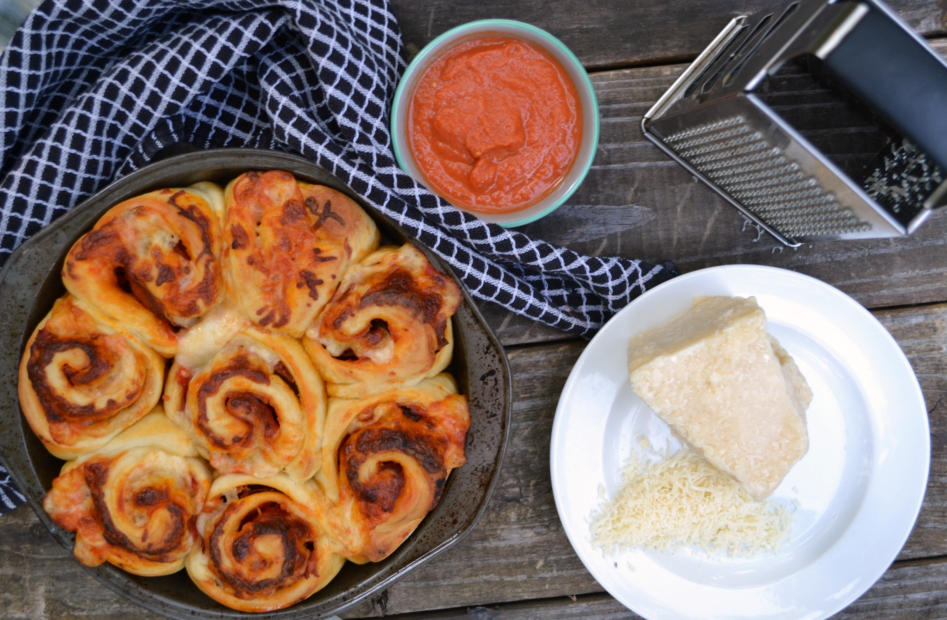 a photo of pepperoni pizza rollips on a wooden table with a blue abd white dish towel and a cup of red sauce