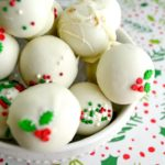 white Eggnog latte truffles with red and green holly sprinkles piled in a white bowl on holly wrapping paper.