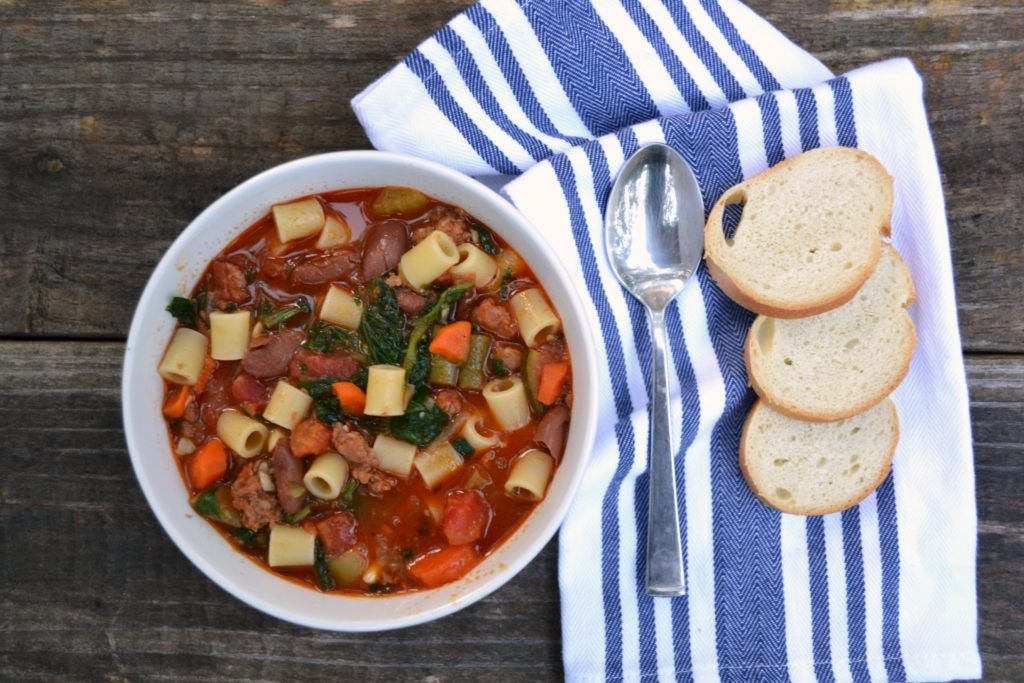 easy minestrone soup in a white bowl on a wooden table with a white and blue striped hand towel topped with sliced bread next to it and a silver spoon