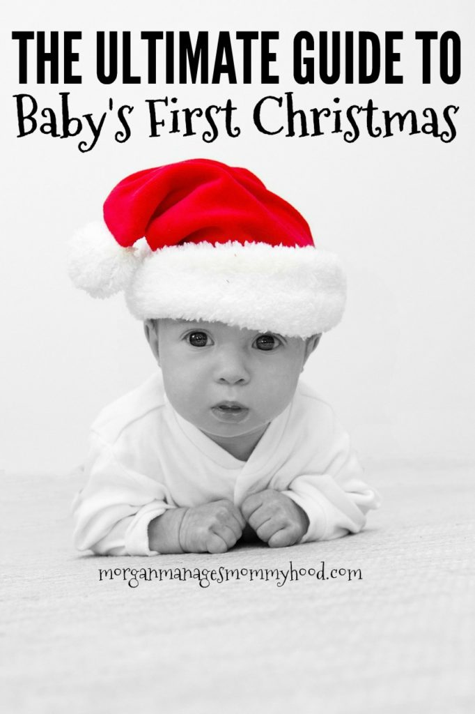 a black and white picture of a baby on his belly on baby's first christmas wearing a red santa ht