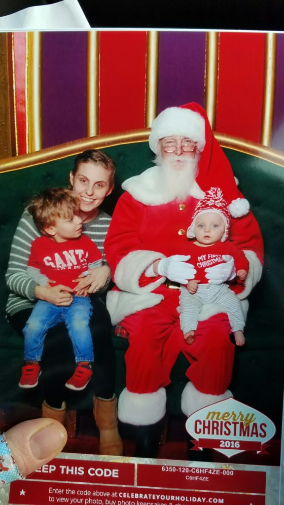 a photo of a woman with a toddler on her lap and a baby on santa's lap celebrating baby's first christmas