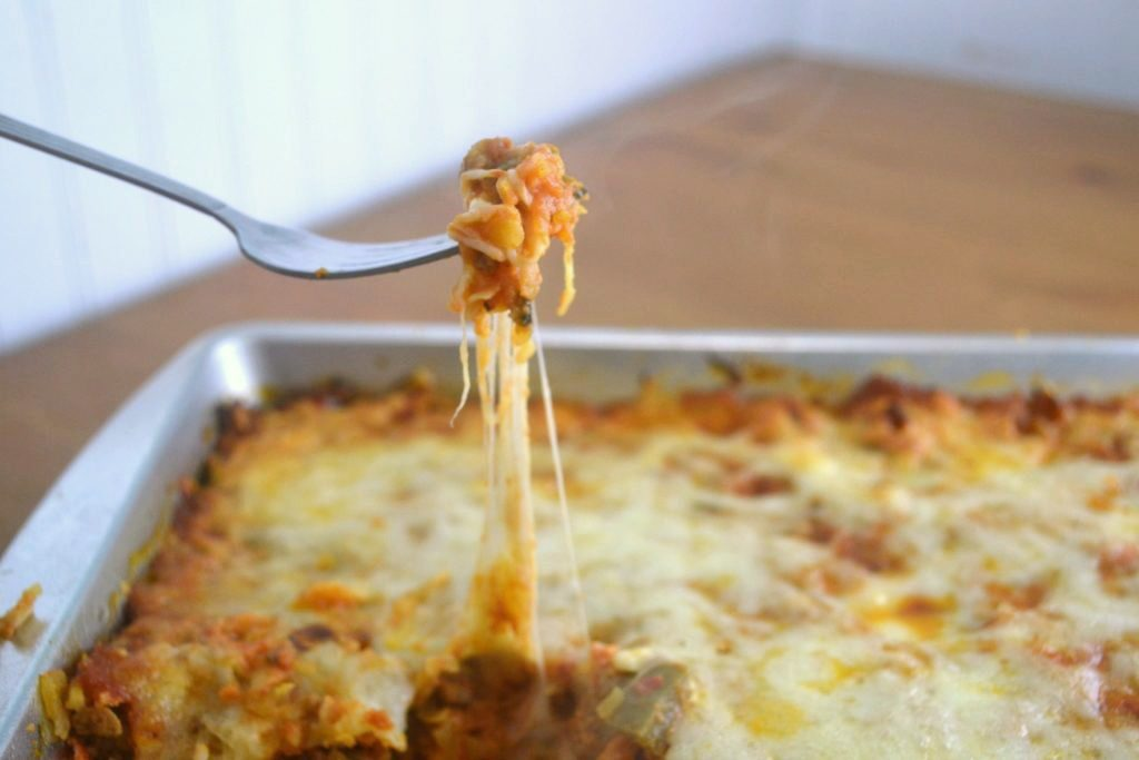 A silver fork pulling a bite of low carb pizza casserole from a silver baking pan with lots of cheese stretching from the pan.