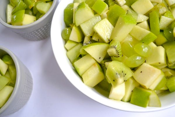 large and small bows in white and grey filled with green fruit salad fro st. patrick's day