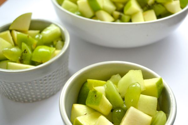 three bowls on a white background filled with green fruit salad