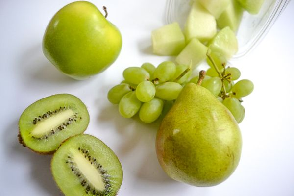 pear, green apple, green grapes, kiwi and honeydew on a white tabletop