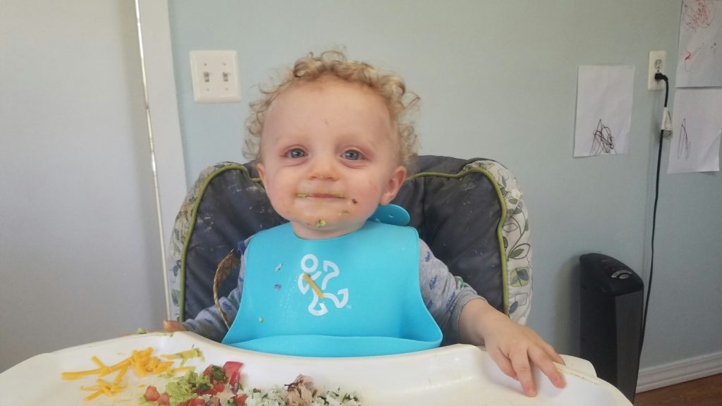 a happy baby in a high chair with a blue bib eating