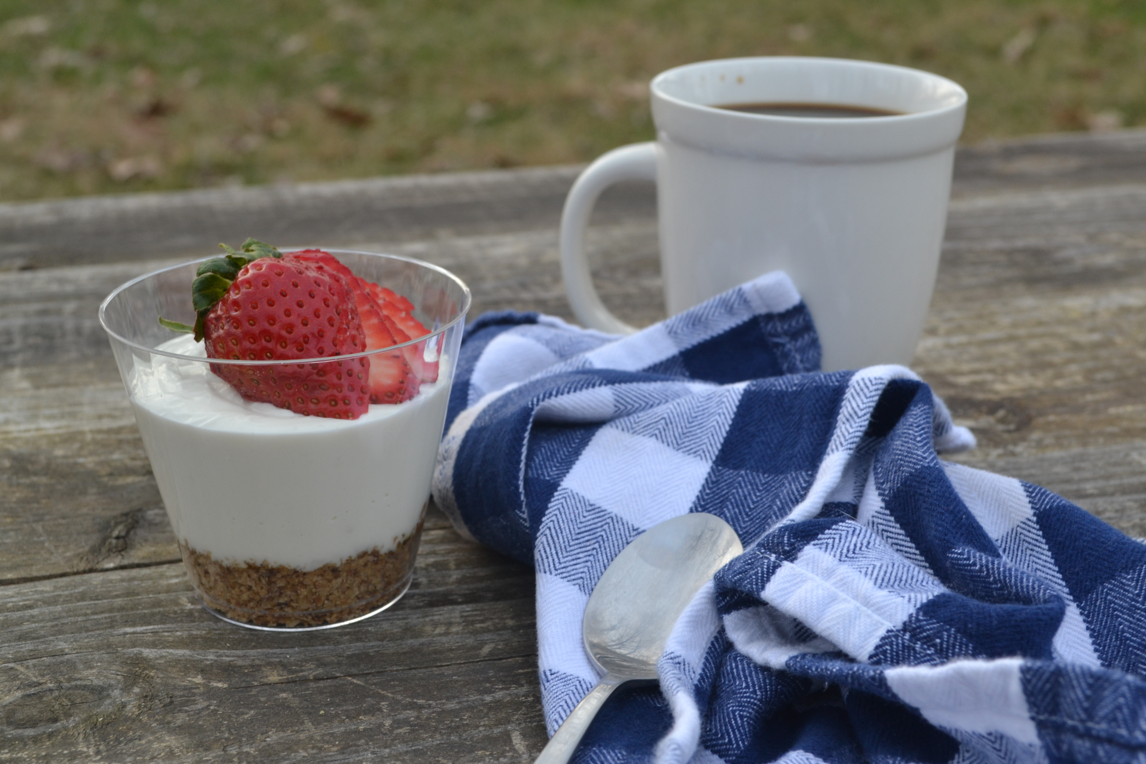 an individual cup of breakfast cheesecake with a strawberry on top on a wooden picnic table with a blue gingham napkin