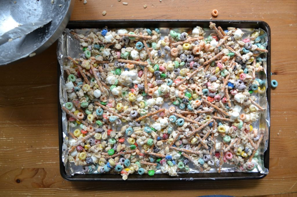 a sheet pan covered in cooling cereal snack mix with froot loops, pretzels, and other sweet and salty ingredients.