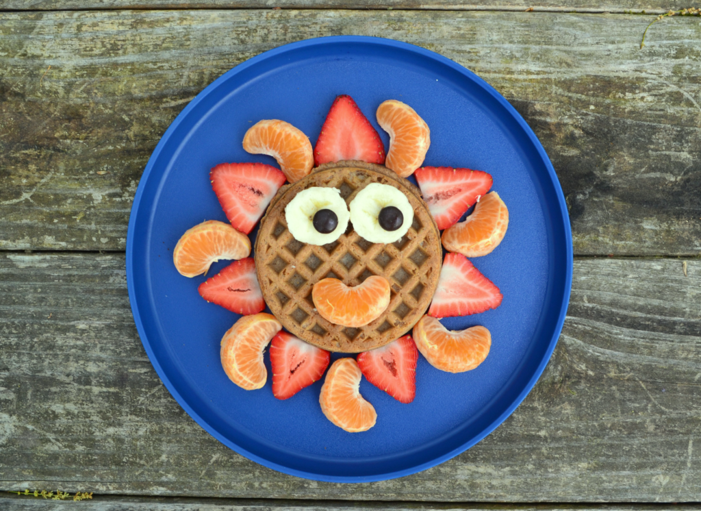 a whole wheat kids waffle made to look like a sun with orange segments, strawberries, and bananas on a blue plate and ona wooden table.