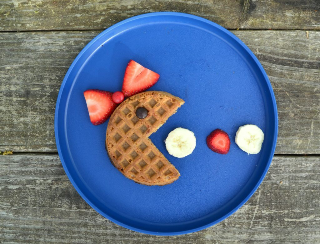 a waffle for kids on a blue plate on a wooden table using a whole wheat waffle, strawberries and bananas made to look like Mrs. Pacman