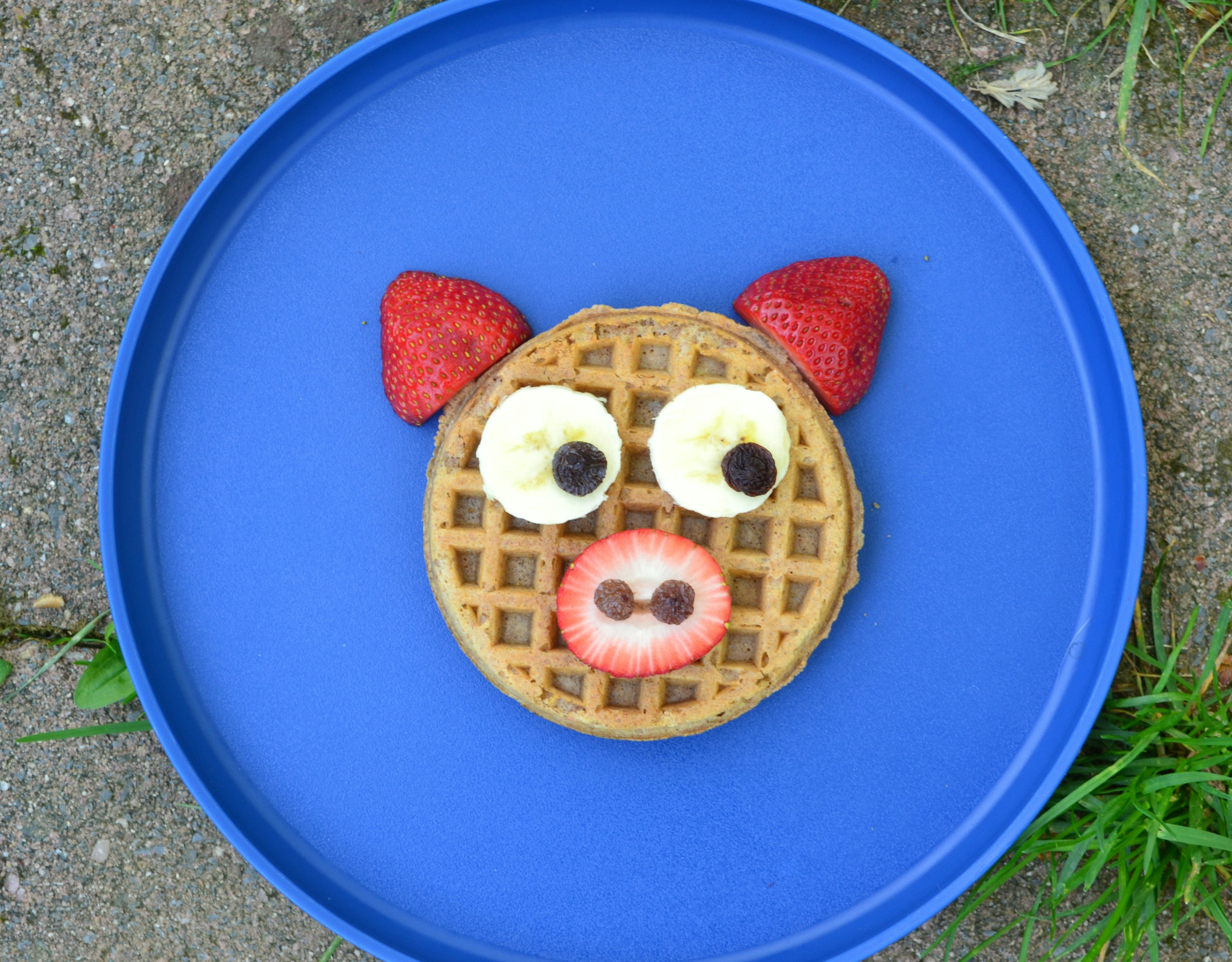 A kids waffle made to look like a pig using bananas and strawberries on a blue plate