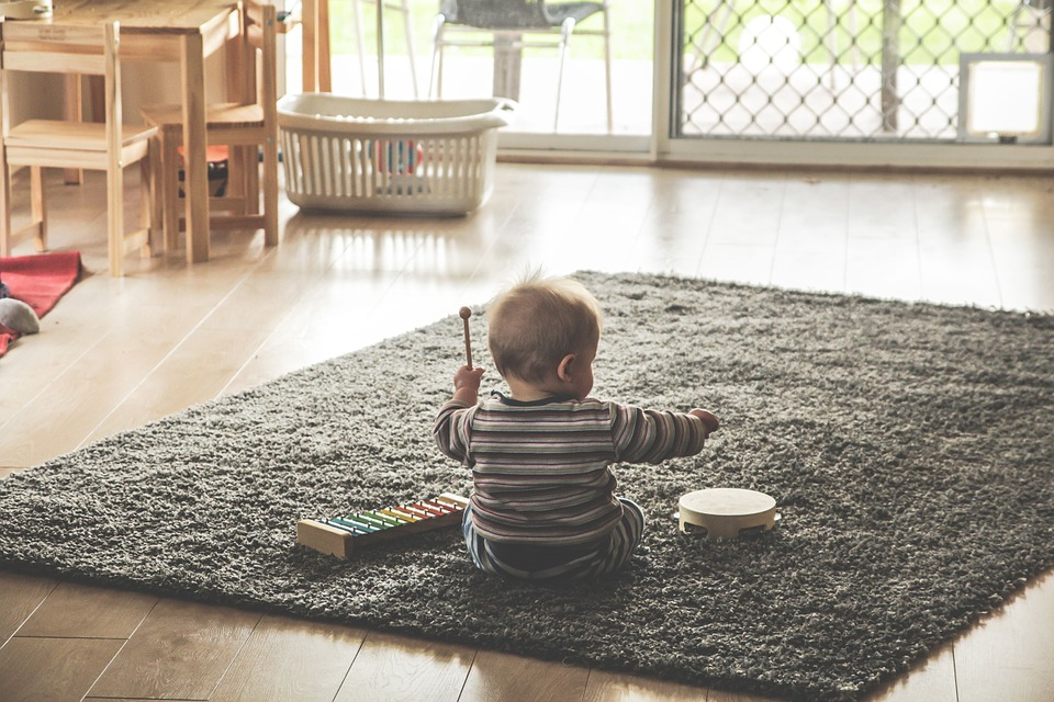 a baby playing an instrument on a fluffy grey carpet