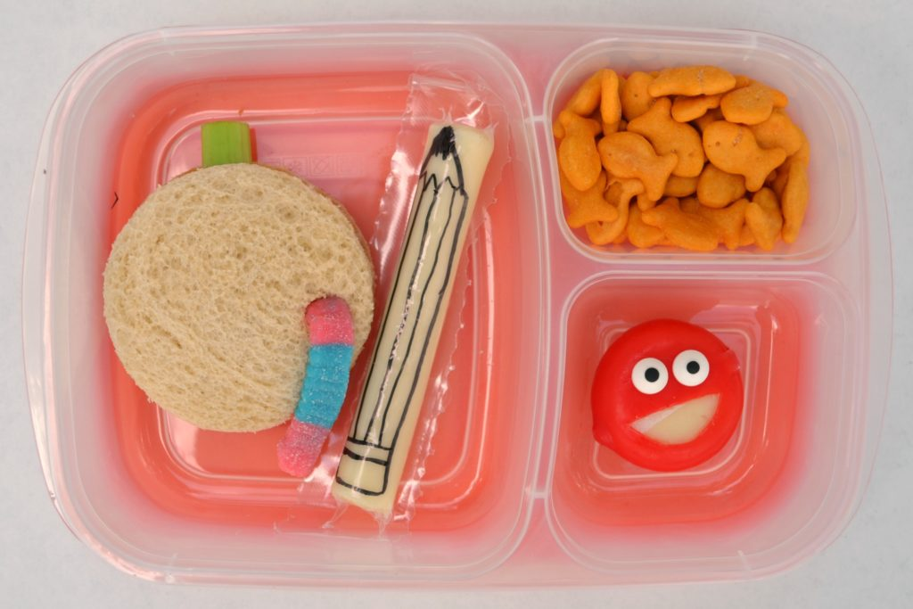 a first day of school lunch with a cheesestick to look like a pencil, sandwich that looks like an apple with a work, and a smiley face cheese