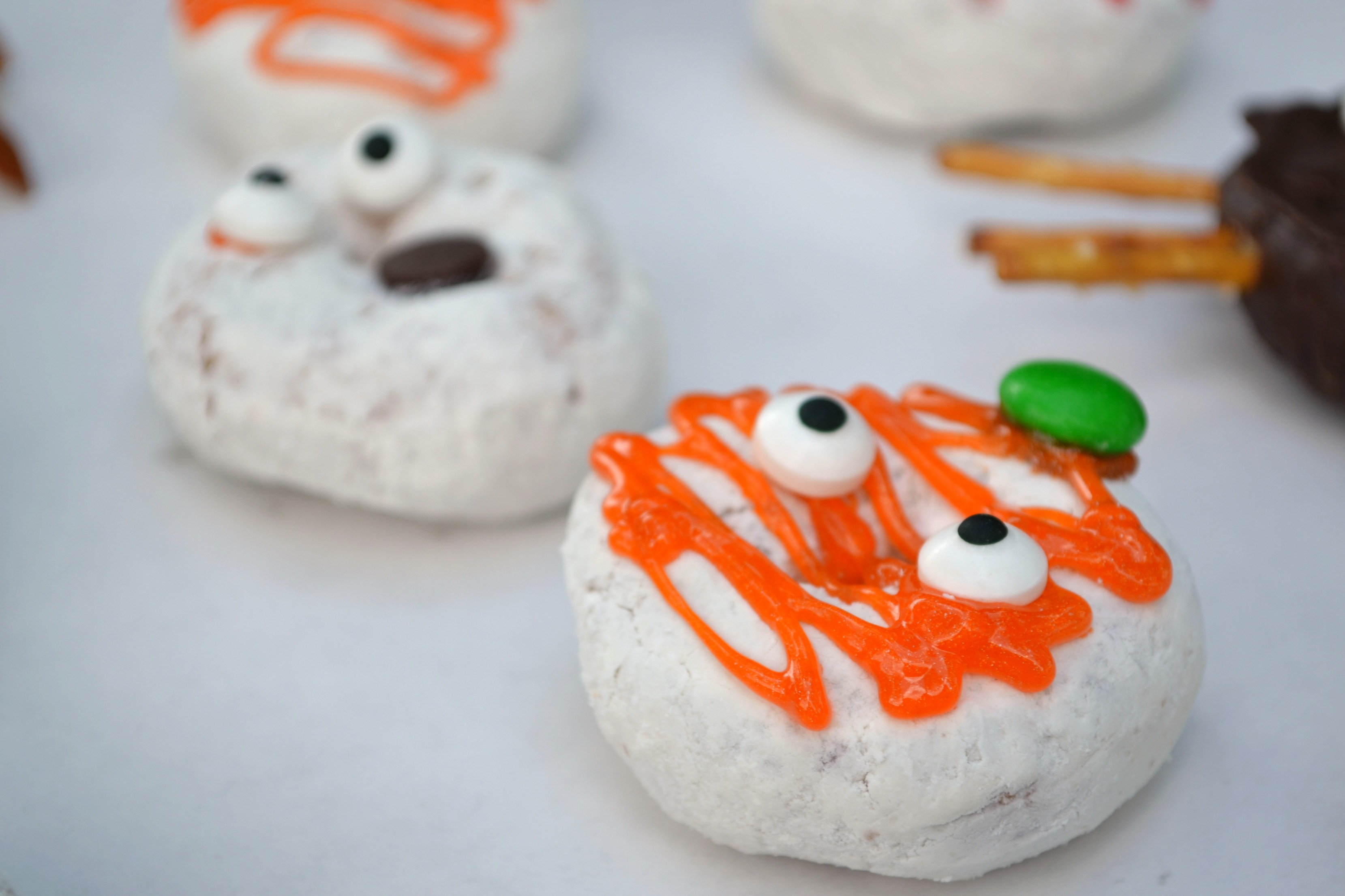 a powdered halloween donuts drizzled in orange frosting with a green mm and candy eyes to make it look like  a pumpkin