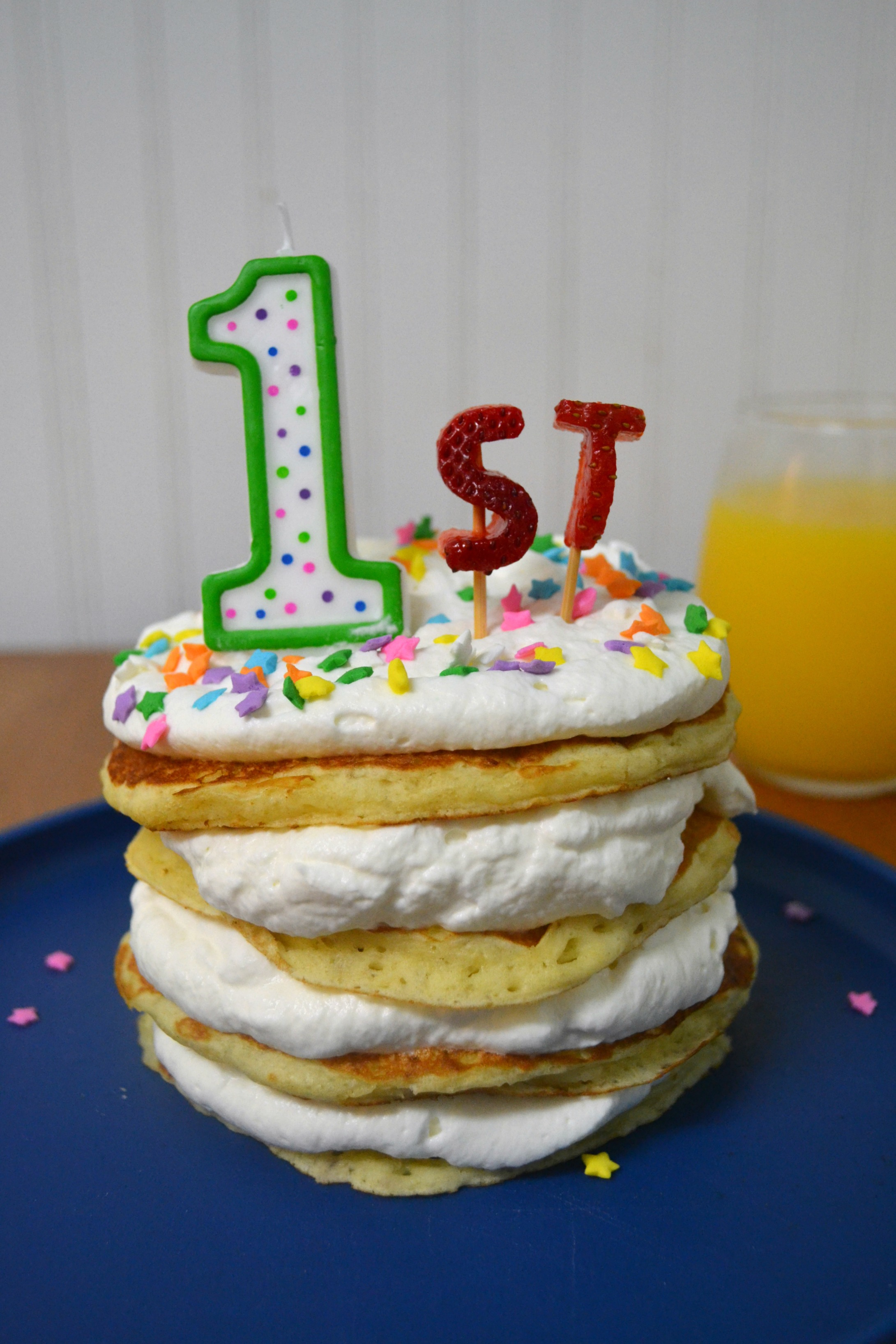 a stack of pancakes with whipped cream, sprinkles, and a #1 candle for the first day of school.