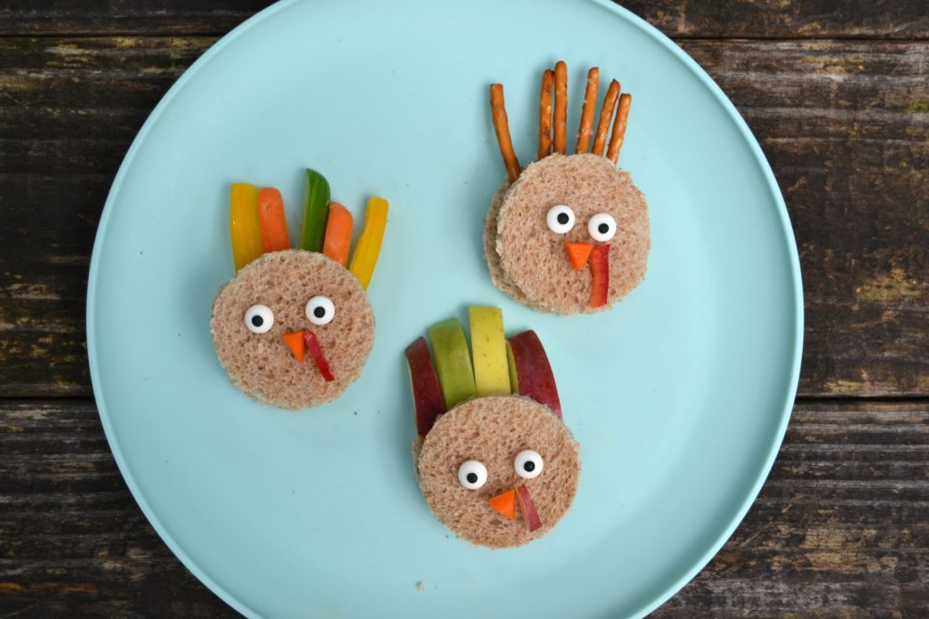3 mini turkey sandwiches for school on a blue plate on a wood picnic table