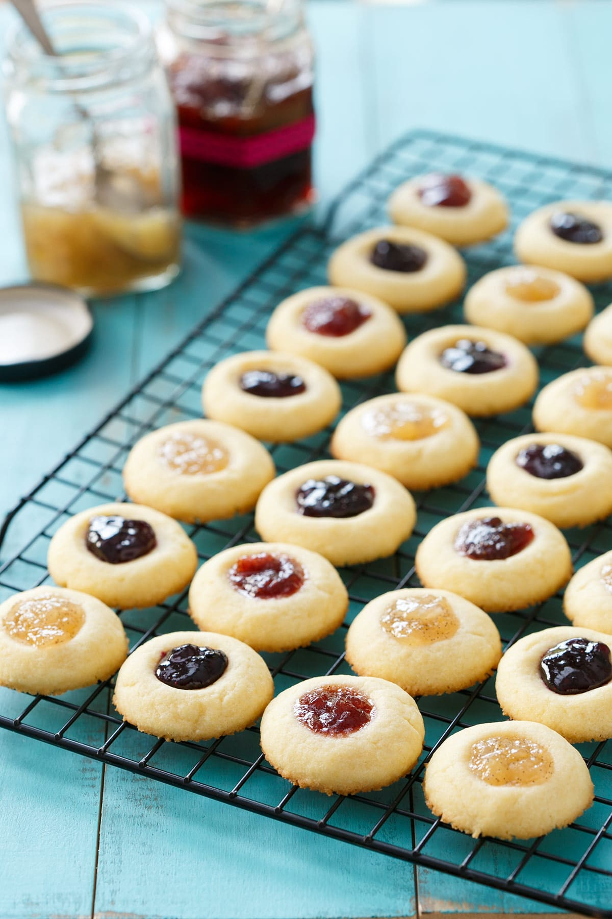 small thumbprint cookies on a wire cooling rack with different kinds of jam in them