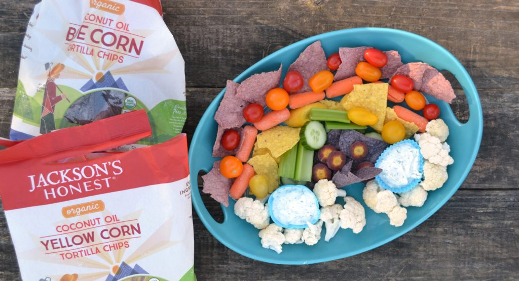 platter of chips and veggies in a rainbow pattern on a blue platter with healthy veggie dip in blue silicone cups on a wooden table next to bags of jackson's honest chips