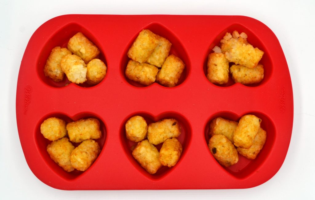 red silicone heart mold with 4 tater tots in each of the 6 cavities.
