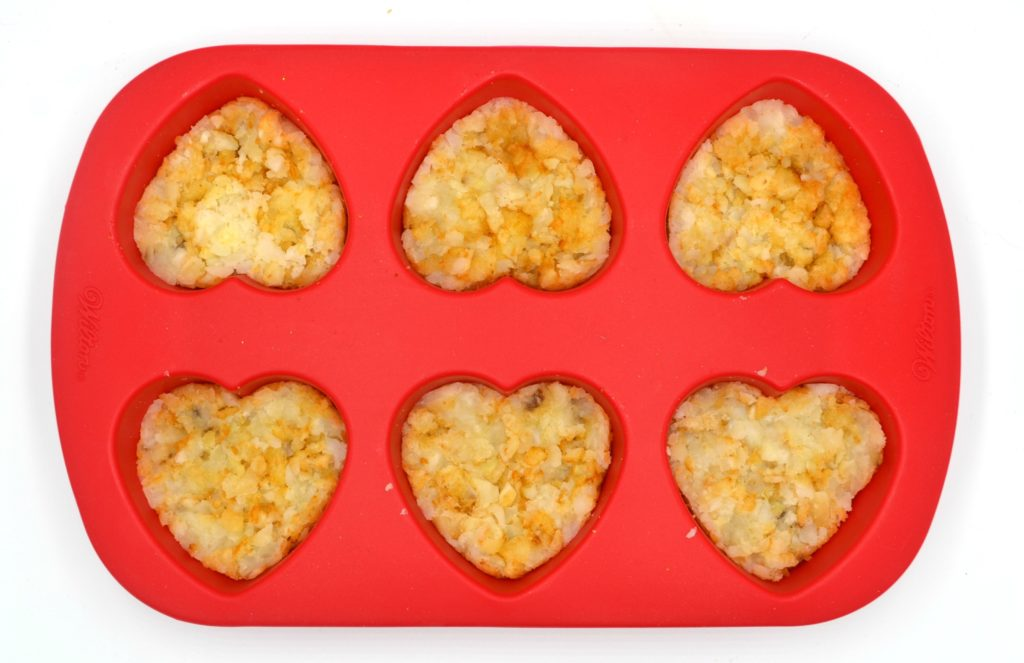 tater tots squished into a red heart shaped silicone mold
