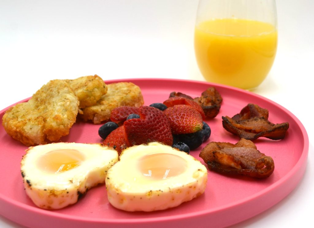 a hearty breakfast of valentines day food on a pink plate. Heart shaped eggs are in the front, with heart hashbrowns, heart shaped fruit salad, and heart bacon behind the eggs on the plate. A glass of orange juice is in the background