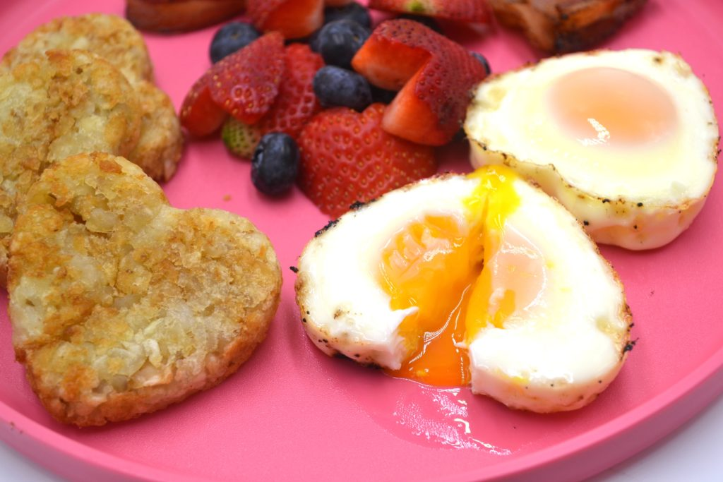 2 heart shaped baked eggs on a pink plate, one is cut in half with the yolk dripping. hear shaped hash browns and heart shaped fruit salad are to the left.