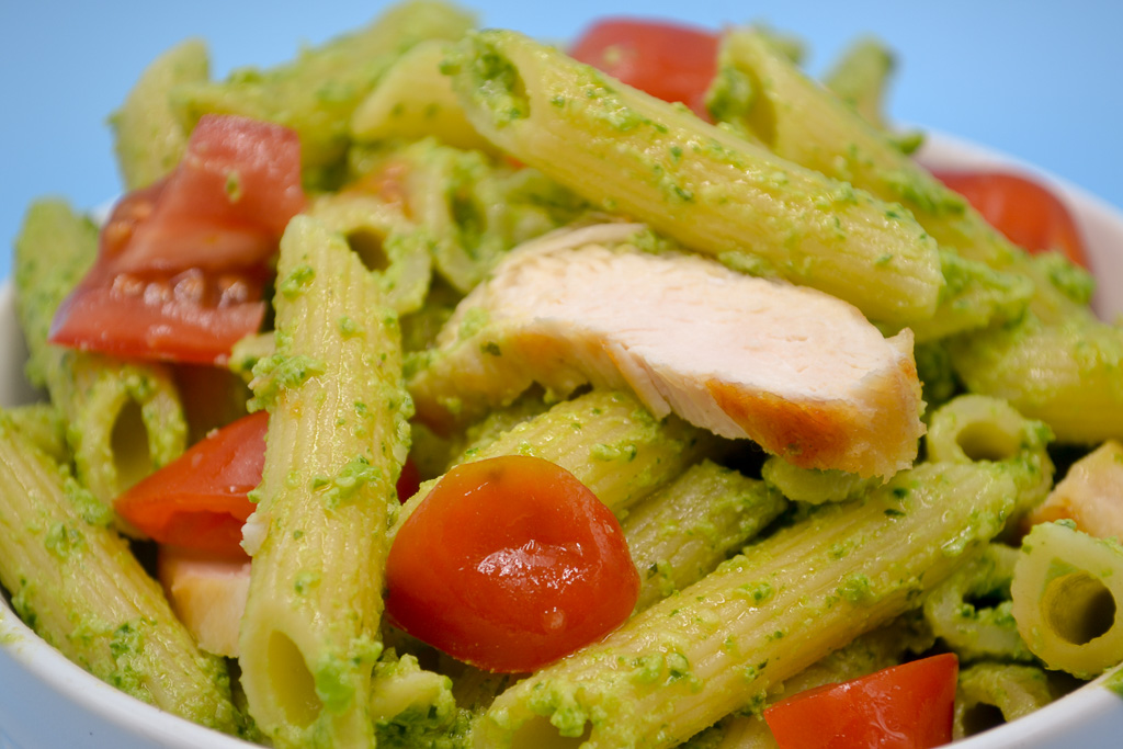 a close up of Veggie Pesto Pasta Sauce. Penne noodles covered in sauce with grilled chicken and red grape tomatos.