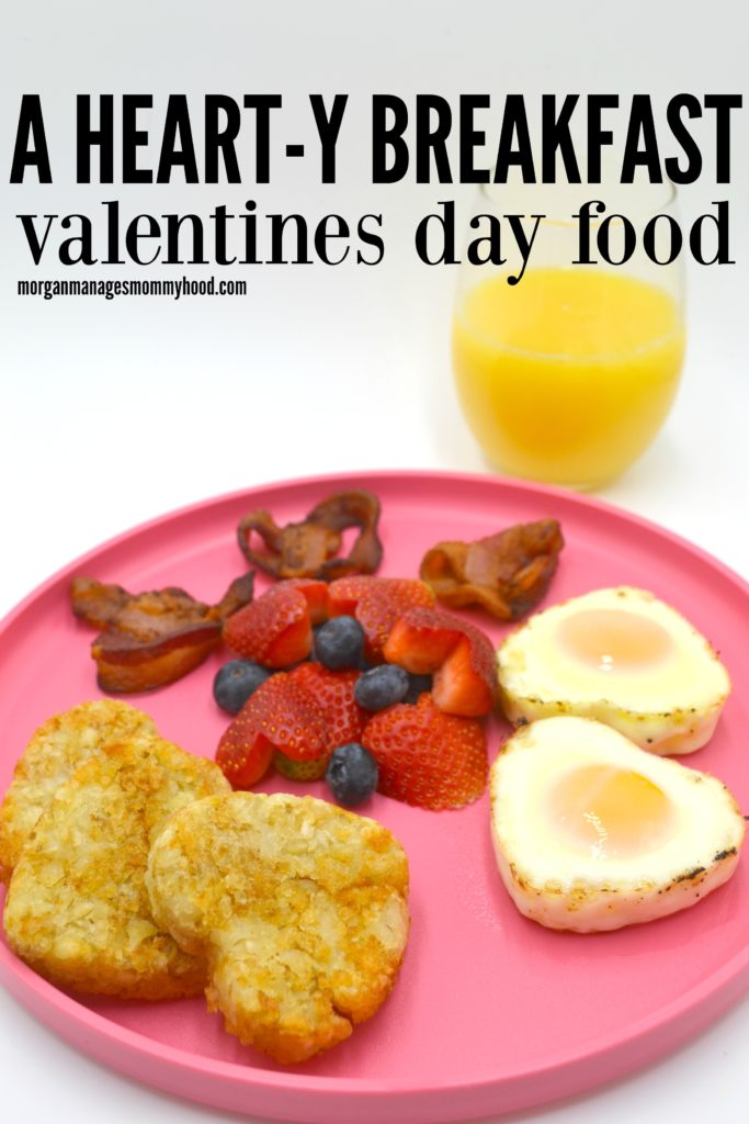 a pink plate with valentines day food on it - hashbrown patties, baked eggs, bacon and fruit salad all in heart shapes with a white background and a glass of orange juice