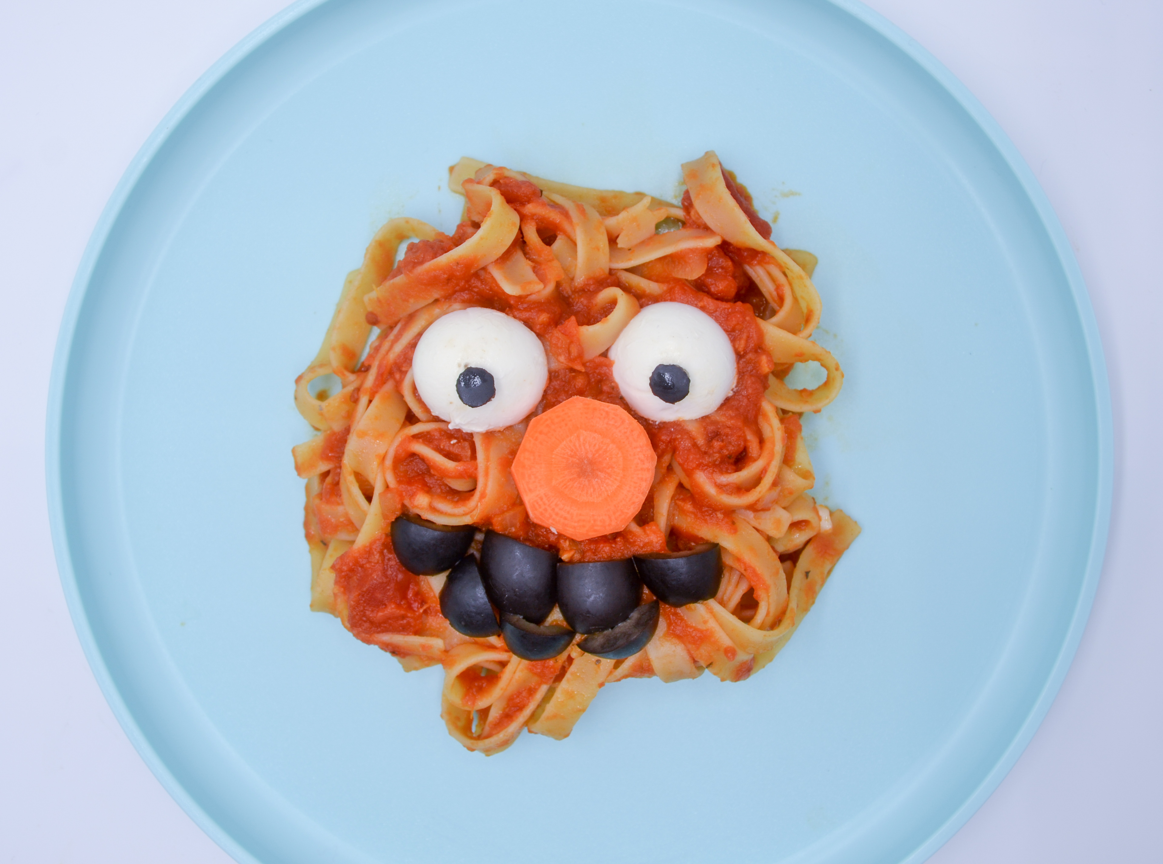 A pile of pasta covered in hidden veggie spaghetti sauce with toppings to make it look like Elmo on a light blue plate