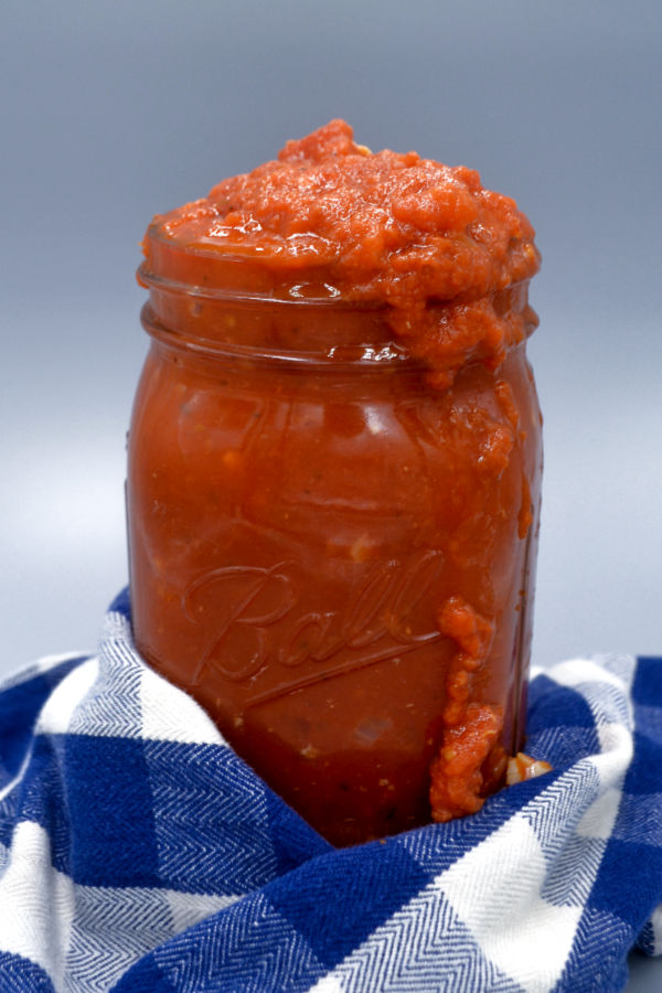 a large mason jar wrapped in a blue and white gingham napkin overflowing with hidden vegetable spaghetti sauce